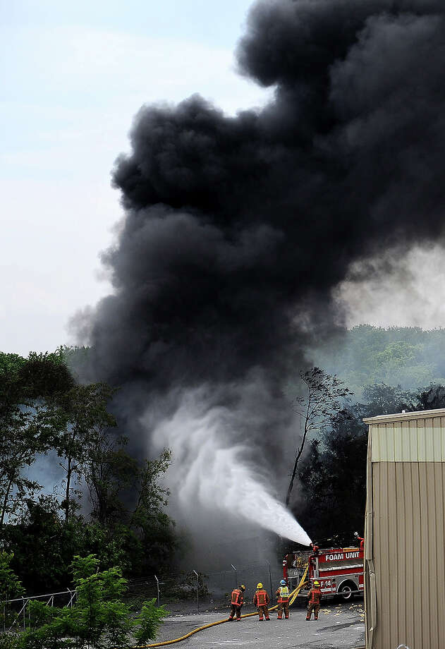As smoke fills the sky, a Foam Unit tries to control a burn on a train derailment that caused a major explosion in the Rosedale neighborhood on May 28, 2013 in Baltimore, Maryland. Residents in nearby neighborhoods were advised to voluntarily evacuate. Photo: Patrick Smith, Getty Images / 2013 Getty Images