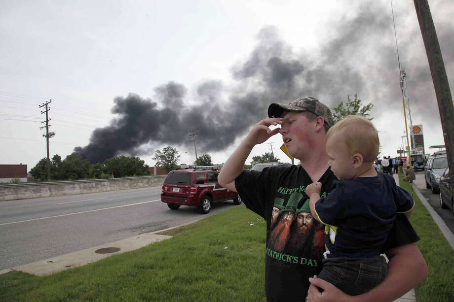 Mark Paugh carries his 15-month-old son Ryan as they watch smoke from a train derailment in White Marsh, Md., Tuesday, May 28, 2013, in Rosedale, Md. A CSX cargo train crashed into a trash truck and derailed Tuesday in a Baltimore suburb and the explosion that followed rattled homes at least a half-mile away and collapsed nearby buildings, setting them on fire, officials and witnesses said. Photo: Charles Dharapak, AP / AP