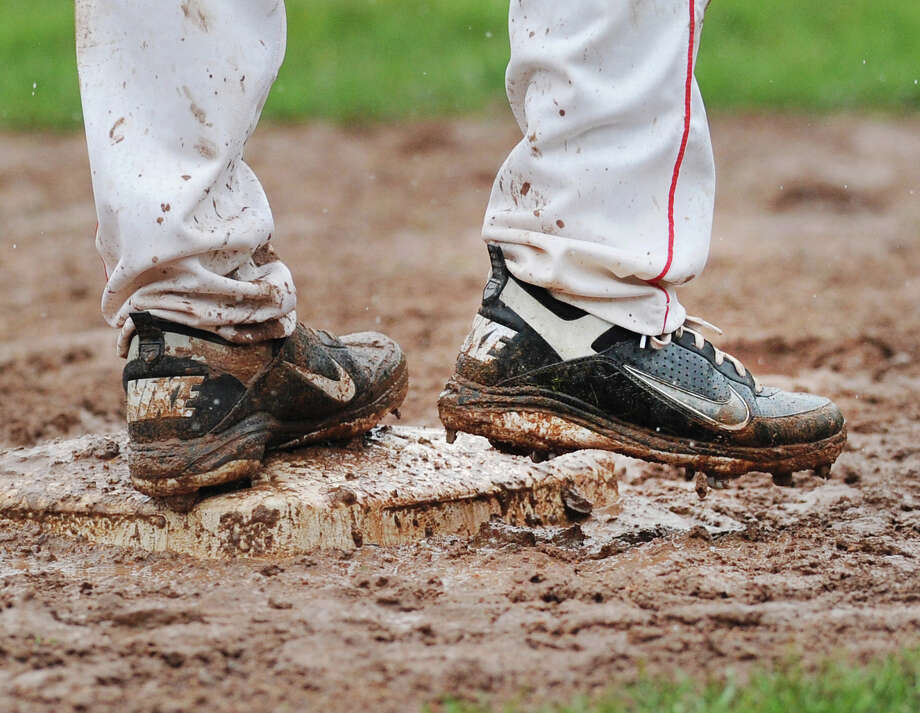 The muddy cleats of Greenwich baseball player Ryota Fujikara tells the story of a rainy Class LL high school baseball playoff game between Greenwich High School and Cheshire High School at Greenwich, Tuesday, May 28, 2013. The game was postponed due to the rain in the bottom of the first inning with the Cardinals leading, 3-1. The game will resume Wednesday at 3:30 p.m. in Greenwich if the field is playable. Photo: Bob Luckey / Greenwich Time
