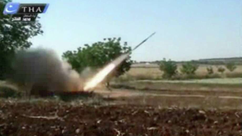 In an image from amateur video, which is consistent with Associated Press reporting, a rocket is fired Tuesday by rebels in Qusair, Syria. Prospects for an arms race in the embattled nation have increased. Photo: Anonymous, HOEP / Ugarit News