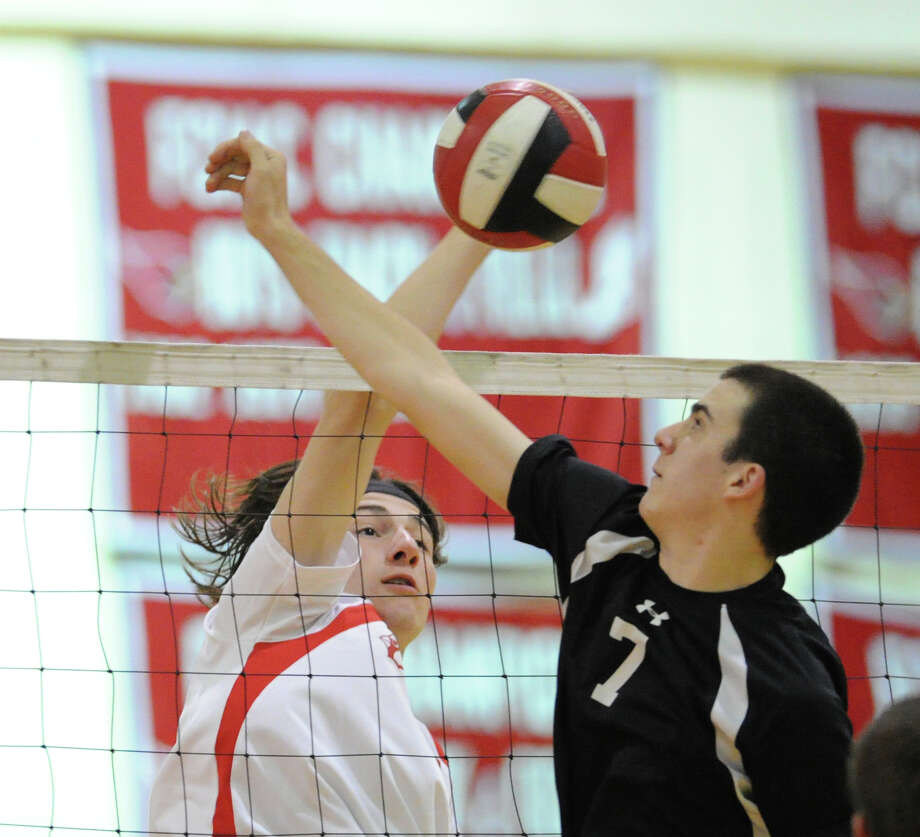 At left, Dexter Frisch of Greenwich spikes the ball past blocking Xavier player Kevin Berger (# 7) during the boys high school Class L volleyball playoff game between Greenwich High School and Xavier High School at Greenwich, Tuesday, May 28, 2013. Xavier won the match, 3-2. Photo: Bob Luckey / Greenwich Time