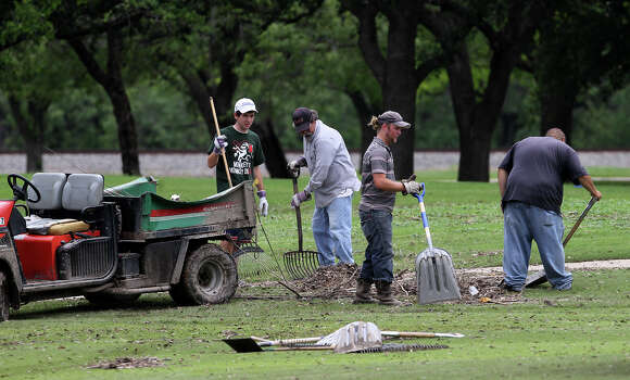 Crews clean up Tuesday May 28, 2013 at Olmos Basin Golf Course after weekend rain flooded the area. A storm Saturday dumped nearly 10 inches of rain across San Antonio and three people died in the flooding. Photo: JOHN DAVENPORT, SAN ANTONIO EXPRESS-NEWS / ©San Antonio Express-News/Photo may be sold to the public