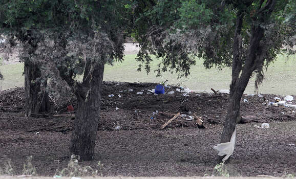Debris and trash has accumulated around trees in an area at Olmos Bason Golf Course after floodwaters swept through the area over the weekend. Photo: JOHN DAVENPORT, SAN ANTONIO EXPRESS-NEWS / ©San Antonio Express-News/Photo may be sold to the public
