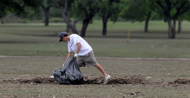 Andrew Braswell picks up trash Tuesday May 28, 2013 at Olmos Basin Golf Course after weekend floowaters swept through the area. Personnel at the course said clean up efforts there should take about a week. Photo: JOHN DAVENPORT, SAN ANTONIO EXPRESS-NEWS / ©San Antonio Express-News/Photo may be sold to the public