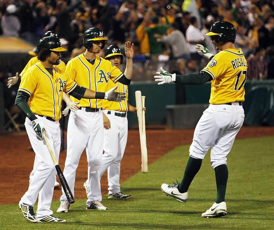 Adam Rosales (right) is congratulated after he finished the A's scoring with a solo home run in the eighth inning. The homer was his third of the season, and ended an 0-for-24 drought. Photo: Carlos Avila Gonzalez, The Chronicle