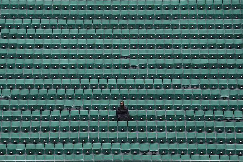 TOPSHOTS A person sits in an empty tribune of the Philippe Chatrier central court as rain falls on the third day of the French tennis Open at the Roland Garros stadium in Paris on May 28, 2013. AFP PHOTO / KENZO TRIBOUILLARDKENZO TRIBOUILLARD/AFP/Getty Images Photo: Kenzo Tribouillard, AFP/Getty Images