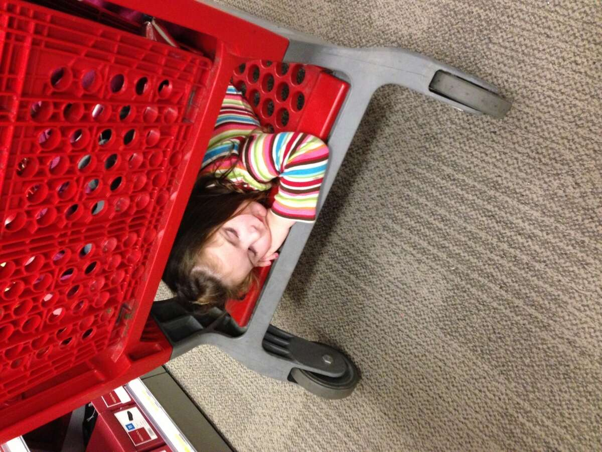 This Target shopper is all tuckered out...underneath the shopping cart.