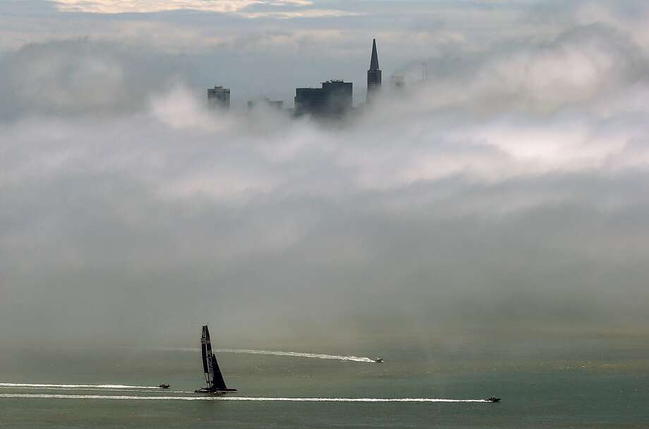 Under a blanket of fog, the Oracle AC72 America's Cup catamaran sails the San 