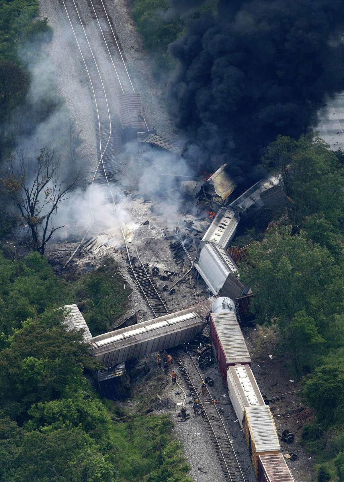 A fire burns at the site of a CSX freight train derailment, Tuesday, May 28, 2013, in White Marsh, Md., where fire officials say the train crashed into a trash truck, causing an explosion that rattled homes at least a half-mile away and collapsed nearby buildings, setting them on fire.