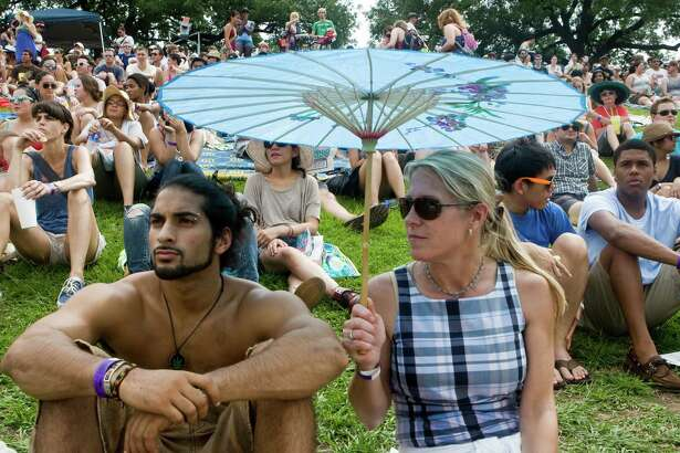 Alex Jayanty (left) and Anne Somerby watch the bands at the Free Press Summer Fest concert on June 5, 2010, in Houston. They brought a parasol to combat the sun. ( Yasmeen Smalley / Chronicle )