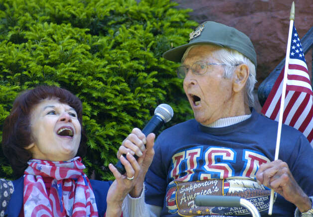 "Francis Hill, 92, a U.S. Navy veteran of World War II, joins with New Milford tax collector Cathy Reynolds to sing ""God Bless America"" during the town's Memorial Day ceremony in New Milford. May 27, 2013 Photo: Norm Cummings"
