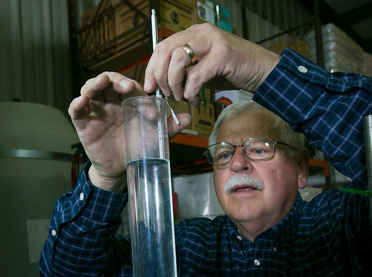 Fog's End Distillery owner Craig Pakish, a retired Monterey County sheriff who grew up in Kentucky, measures the proof of the alcohol in one of his spirits. He distills corn to produce his California Moonshine and rye to produce his Monterey Rye at the distillery in Gonzales.