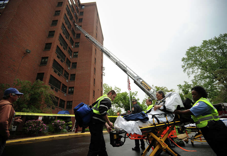 A resident is transported to an ambulance outside a high rise fire at Sycamore Place Apartments at 285 Maplewood Avenue in Bridgeport, Conn. on Wednesday, May 29, 2013. Photo: Brian A. Pounds / Connecticut Post