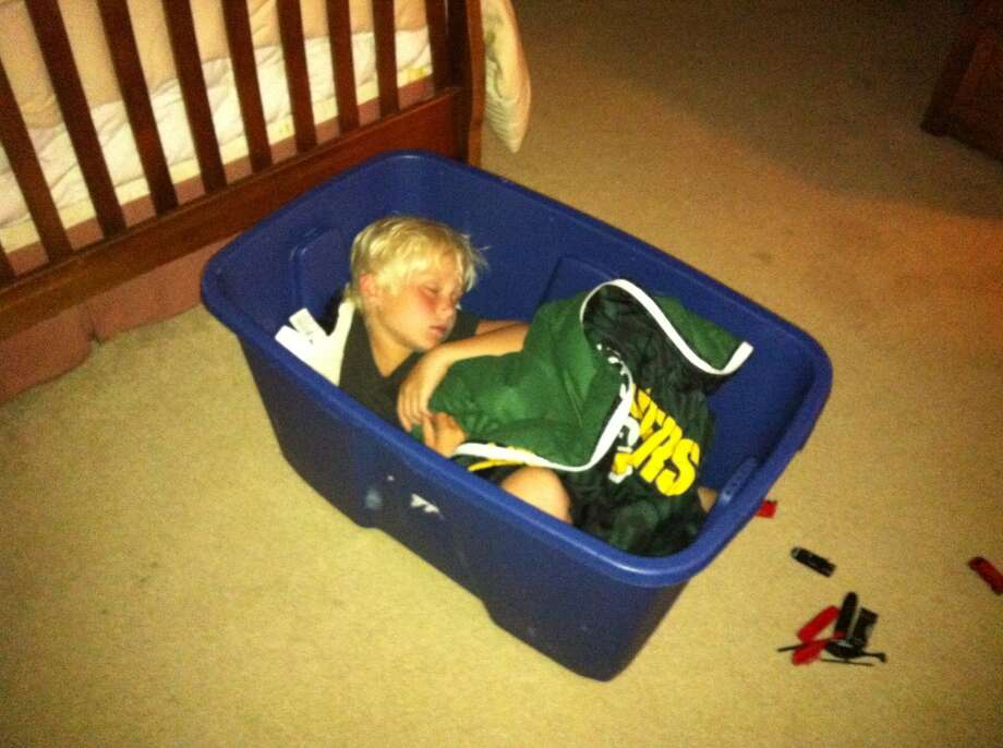 This 7-year-old boy was watching an NBA playoff game with his Dad when he fell asleep in a storage bin. Photo: Bryan Bickford