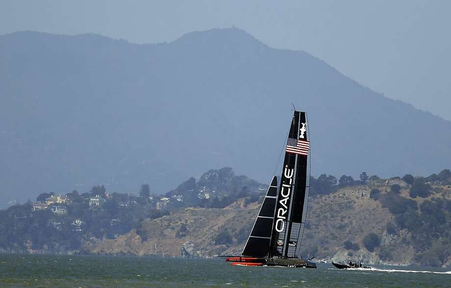 Oracle Team USA trains for the America's Cup with Mt. Tamalpais in the background Thursday, May 23, 2013 in San Francisco. Body armor and high-visibility helmets for crew members are among the recommendations made by a group of sailing experts addressing safety concerns in the America's Cup. The group led by regatta director Iain Murray unveiled 37 proposals on Wednesday, two weeks after a member of the Artemis Racing crew died when the catamaran capsized during a training run on San Francisco Bay. (AP Photo/Eric Risberg) Photo: Eric Risberg, Associated Press