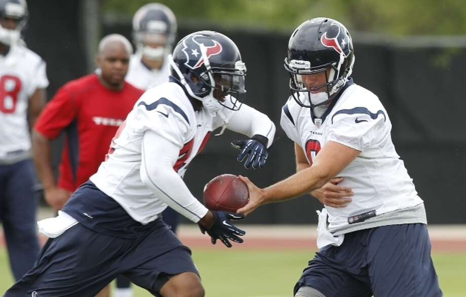 Ben Tate takes a handoff from quarterback Matt Schaub during Wednesday's organized team activities at the Methodist Training Center.