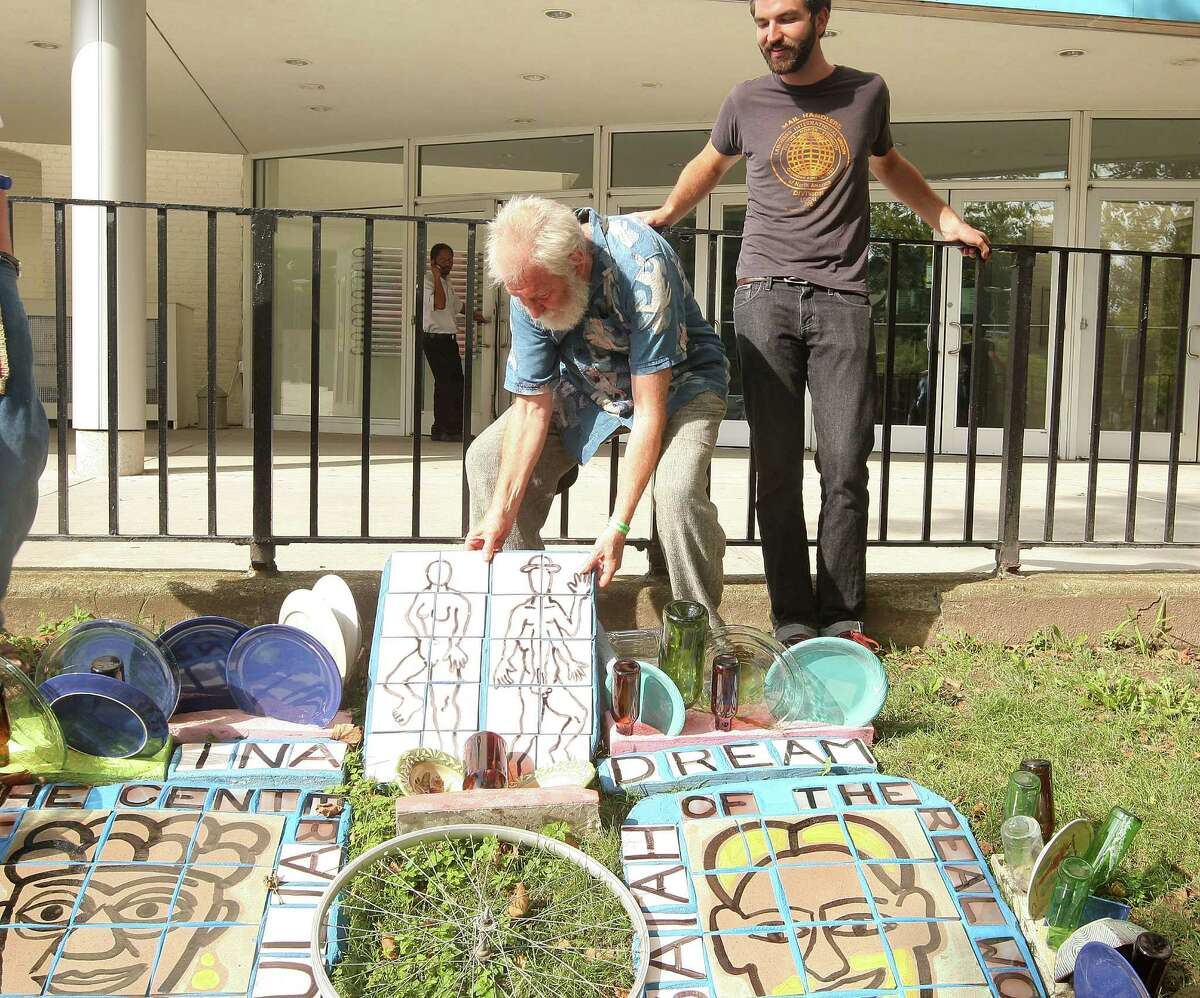 """NEW YORK - AUGUST 23: (L-R) Artist, film subject Isaiah Zagar fixes his mosaic installation outside the Brooklyn Museum while his son, director Jeremiah Zagar looks on during the HBO documentary screening of """"In A Dream"""" on August 23, 2009 in the Borough of Brooklyn, New York City. (Photo by Michael Loccisano/Getty Images for HBO)"""