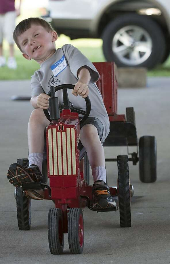 The little farmer that could: Six-year-old Joshua Kernodle musters every ounce of strength for the Pedal Pull competition at the Boyle County Fair in Danville, Ky. Photo: Clay Jackson, Associated Press