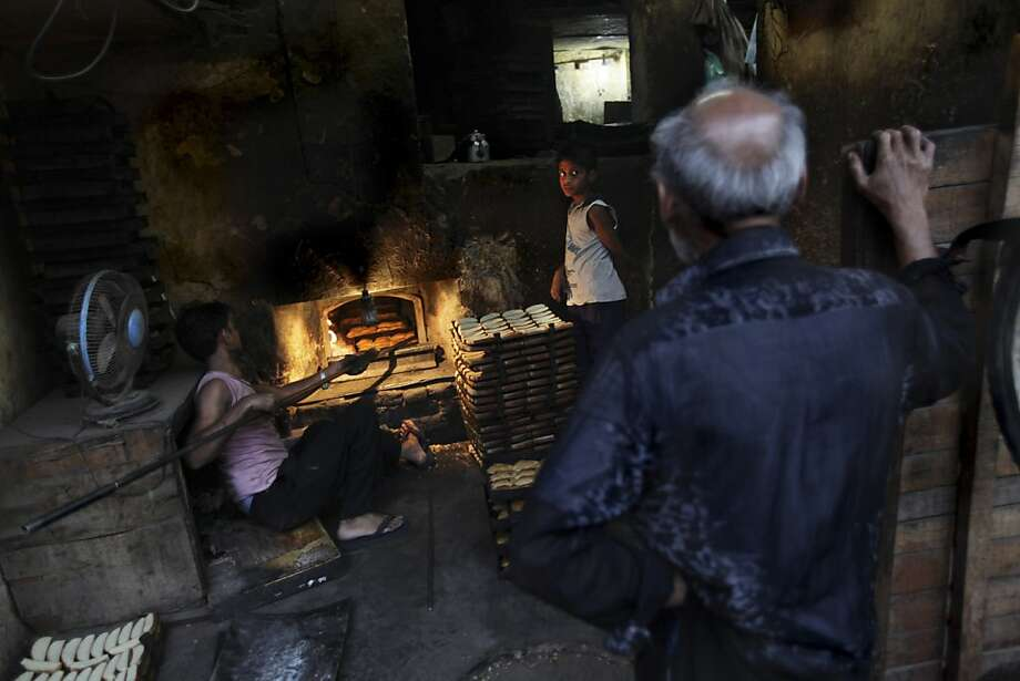 Fresh out of the oven: A customer waits for service as a baker checks his 