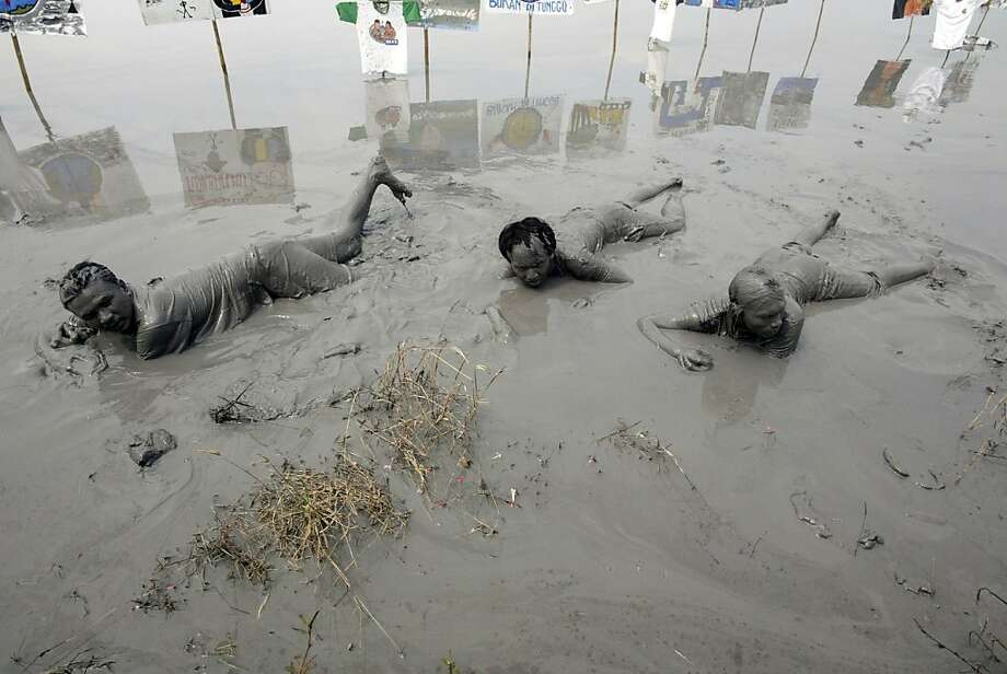 Sludge victims: Indonesian villagers who lost their homes to a mud volcano immerse themselves in the volcano's muck in Sidoarjo, Java. They were dramatizing their suffering during a protest marking the seventh year of the ecological disaster. Experts believe the gas drilling company Lapindo Brantas, controlled by the family of powerful tycoon Aburizal Bakrie, was responsible for the catastrophe, which permanently buried 12 villages. Photo: Juni Kriswanto, AFP/Getty Images