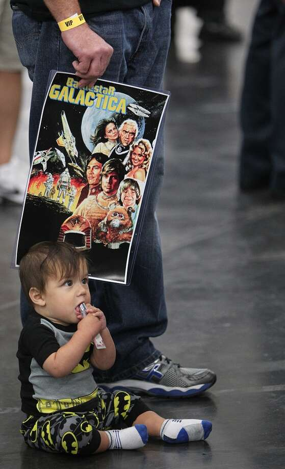 A tiny comic fan sits in line with family.