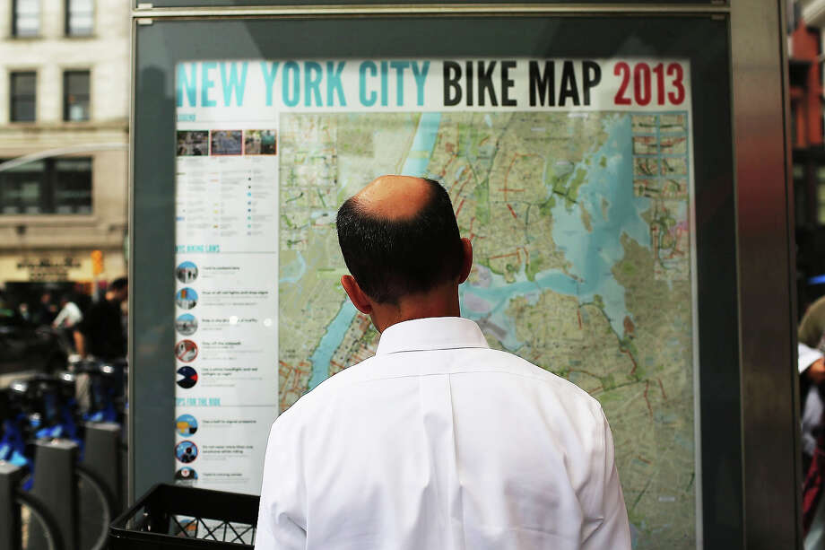 A man looks at a bicycle map at a Citi Bike docking station in Union square on May 29, 2013 in New York City. Citi Bike, the long awaited bike sharing program that launched over the Memorial Day weekend in New York, provides 6,000 bikes which are available for short-term rental at 330 stations in Manhattan below 59th Street and parts of Brooklyn. Until June 2nd only members of the Citi Bike program can use the bikes. The bikes will rent daily for $9.95 (plus tax ) or weekly for $25 and will be limited to trips of 30 minutes each. More than 16,000 people have signed up to be members so far. Photo: Spencer Platt, Getty Images / 2013 Getty Images