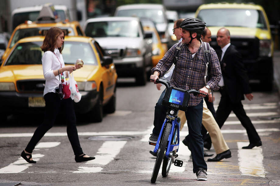 A man rides a Citi Bike on May 29, 2013 in New York City. Citi Bike, the long awaited bike sharing program that launched over the Memorial Day weekend in New York, provides 6,000 bikes which are available for short-term rental at 330 stations in Manhattan below 59th Street and parts of Brooklyn. Until June 2nd only members of the Citi Bike program can use the bikes. The bikes will rent daily for $9.95 (plus tax ) or weekly for $25 and will be limited to trips of 30 minutes each. More than 16,000 people have signed up to be members so far. Photo: Spencer Platt, Getty Images / 2013 Getty Images