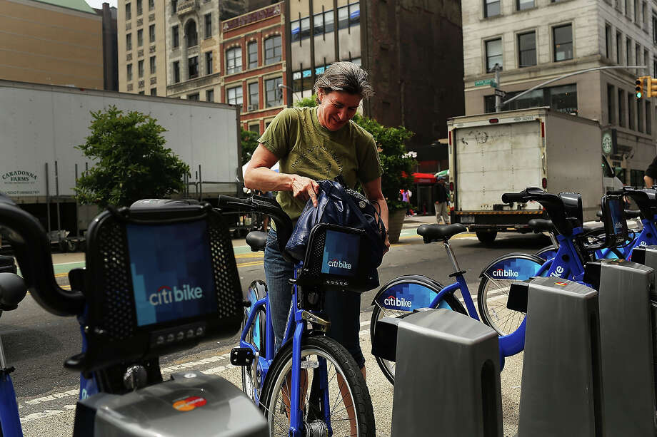 Julie Iovine returns a Citi Bike to a docking station in Union square on May 29, 2013 in New York City. Citi Bike, the long awaited bike sharing program that launched over the Memorial Day weekend in New York, provides 6,000 bikes which are available for short-term rental at 330 stations in Manhattan below 59th Street and parts of Brooklyn. Until June 2nd only members of the Citi Bike program can use the bikes. The bikes will rent daily for $9.95 (plus tax ) or weekly for $25 and will be limited to trips of 30 minutes each. More than 16,000 people have signed up to be members so far. Photo: Spencer Platt, Getty Images / 2013 Getty Images