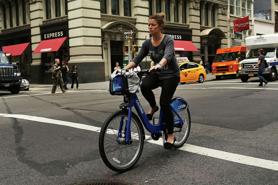 A woman rides a Citi Bike on May 29, 2013 in New York City. Citi Bike, the long awaited bike sharing program that launched over the Memorial Day weekend in New York, provides 6,000 bikes which are available for short-term rental at 330 stations in Manhattan below 59th Street and parts of Brooklyn. Until June 2nd only members of the Citi Bike program can use the bikes. The bikes will rent daily for $9.95 (plus tax ) or weekly for $25 and will be limited to trips of 30 minutes each. More than 16,000 people have signed up to be members so far. Photo: Spencer Platt, Getty Images / 2013 Getty Images