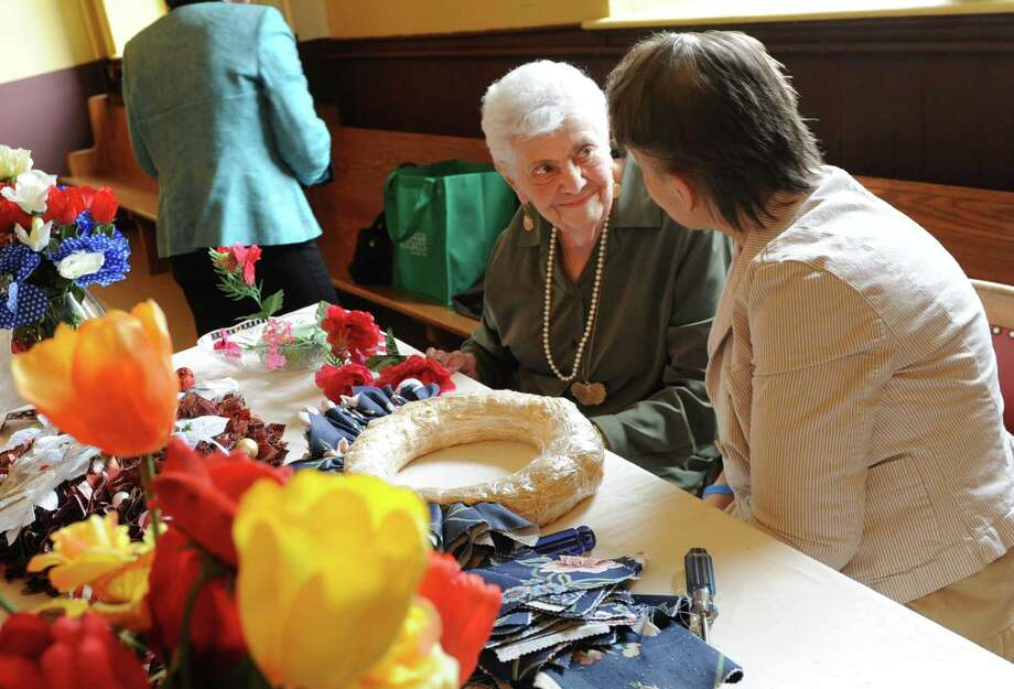Margaret Rufer, 92, left, of Schenectady teaches Trish Van Deusen, 61, of Schenectady how to make artificial floral wreaths in the ?Tapping into the Arts,? program at the Schenectady Light Opera Company on Tuesday, May 28, 2013 in Schenectady, N.Y. Schenectady County Senior and Long Term Care, Schenectady ARC and the Schenectady Light Opera Company partner to create the ?Tapping into the Arts,? program. (Lori Van Buren / Times Union) Photo: Lori Van Buren / 00022581A