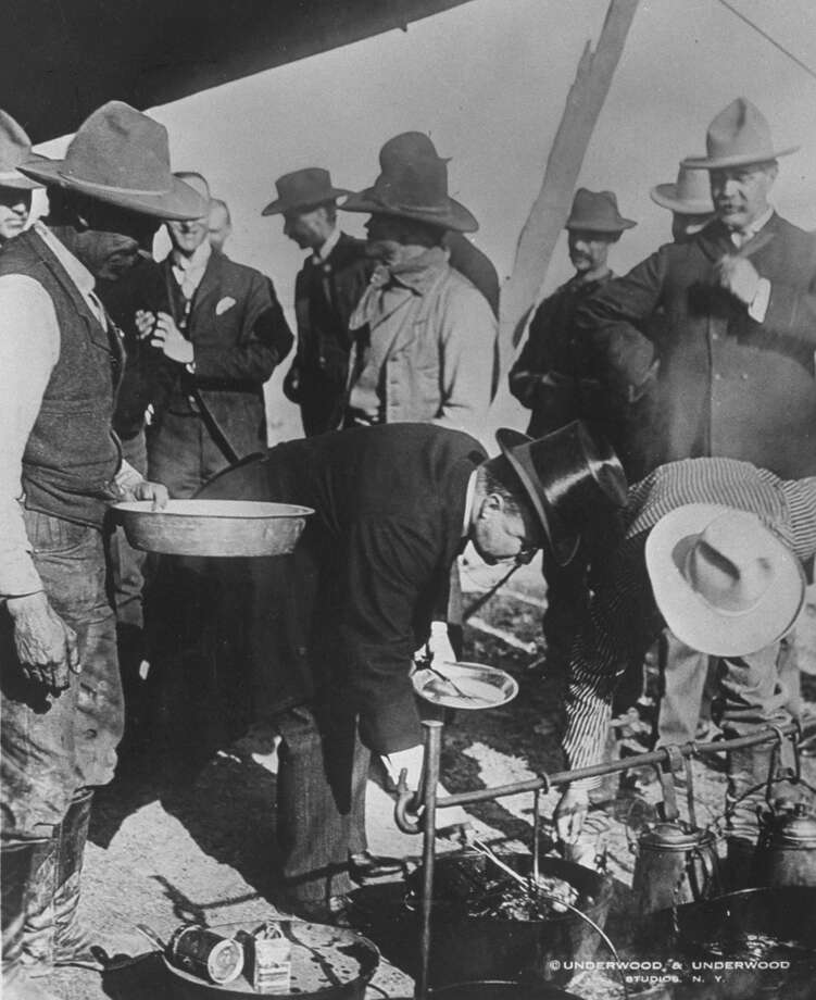 Theodore Roosevelt, dressed in a top hat, is pictured helping himself to a chuck-wagon breakfast at a camp in Hugo, Colorado in 1903, during his eight-week tour of the American West, which included a stop in Seattle. (Photo: Underwood and Underwood/Getty Images) Photo: - / Time & Life Pictures
