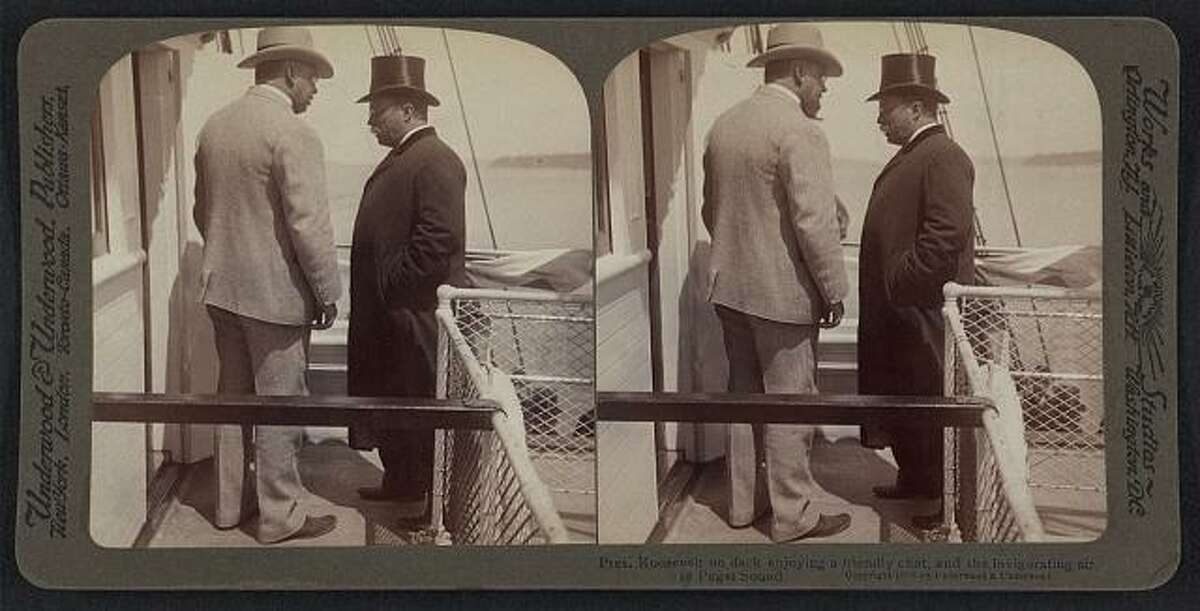 """Roosevelt arrived by the steamship Spokane, which docked in Seattle on May 23, 1903. The caption on this 1903 photo reads: """"Pres. Roosevelt on deck enjoying a friendly chat and the invigorating air of Puget Sound."""" (Photo: Library of Congress)."""