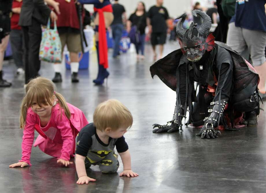 "Adrienne Reif, dressed as a ""Mabh,"" plays with her daughter Lillith, 3, and son Liam, 2."