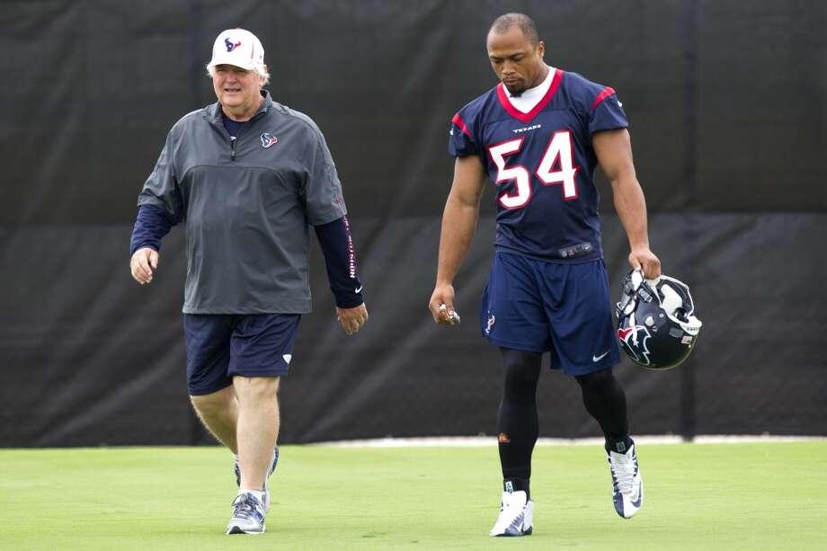 Texans defensive coordinator Wade Phillips, left, walks onto the field with linebacker Trevardo Williams.