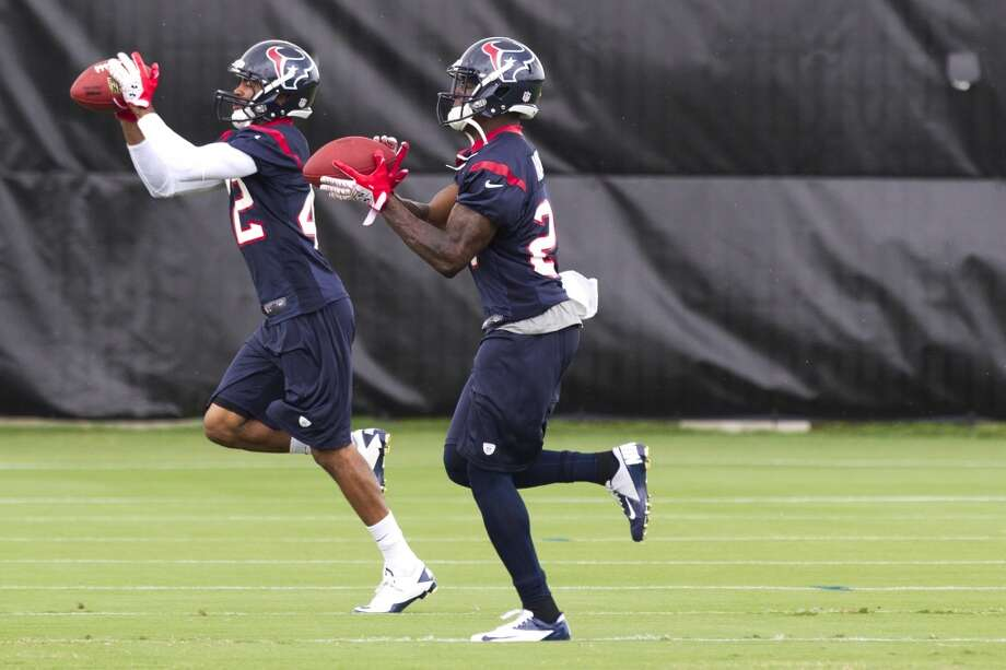 Texans defensive backs Johnny Adams (42) and Travis Howard run a drill.