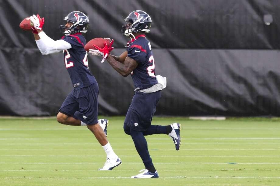 Texans defensive backs Johnny Adams (42) and Travis Howard run a drill.