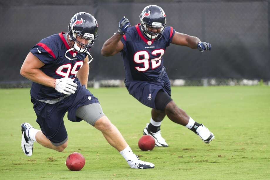 Texans defensive linemen J.J. Watt (99) and Earl Mitchell (92) run a drill.