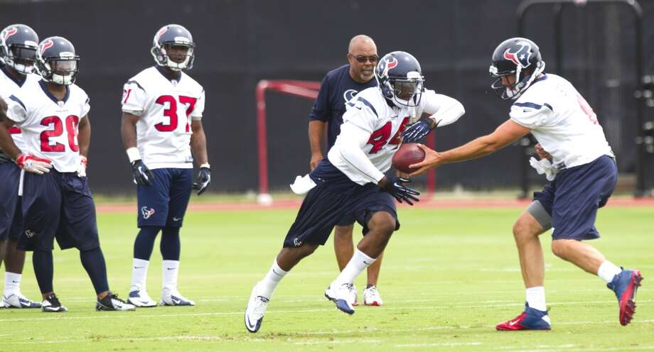 Texans running back Ben Tate (44) takes a handoff from quarterback Matt Schaub (8) as Dennis Johson (28) and Ray Graham (37) and running backs coach Chick Harris look on.