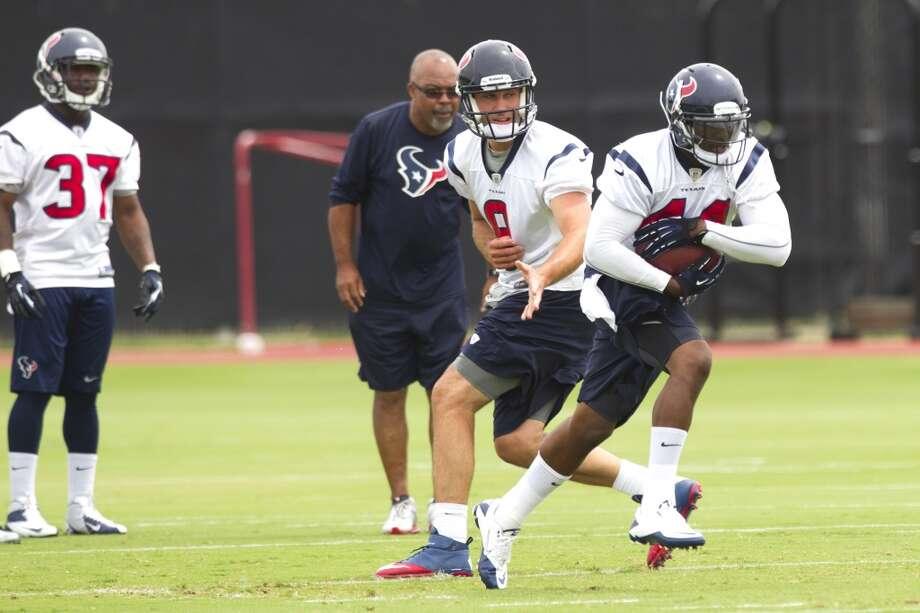 Texans running back Ben Tate (44) takes a handoff from quarterback Matt Schaub (8) as Ray Graham (37) and running backs coach Chick Harris look on.