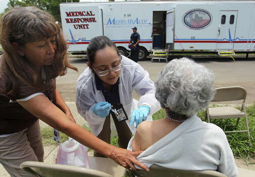 Metro Health's Audrey Munoz gives a hepatitis vaccine to 91-year-old Tolina Doublet along Barbara Street on Wednesday, May 29, 2013. Metro Health issued tetanus and hepatitis vaccinations in parts of the city hardest hit by last weekend's floods. A mobile unit was sent out with a medical crew to give tetanus and hepatitis vaccines to people living or working in areas that were affected. Officials said the mobile unit has been out since Tuesday. Photo: Kin Man Hui, San Antonio Express-News / © 2013 San Antonio Express-News