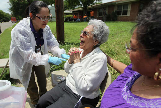 91-year-old Tolina Doublet (center) gives thanks as Metro Health's Audrey Munoz prepares to give Doublet a tetanus shot along Barbara Street on Wednesday, May 29, 2013. Metro Health issued tetanus and hepatitis vaccinations in parts of the city hardest hit by last weekend's floods. A mobile unit was sent out with a medical crew to give tetanus and hepatitis vaccines to people living or working in areas that were affected. Officials said the mobile unit has been out since Tuesday. Photo: Kin Man Hui, San Antonio Express-News / © 2013 San Antonio Express-News