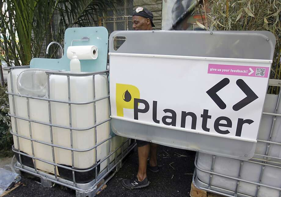 Darryl Smith demonstrates how the PPlanter operates in the Tenderloin National Forest art project. Photo: Paul Chinn, The Chronicle