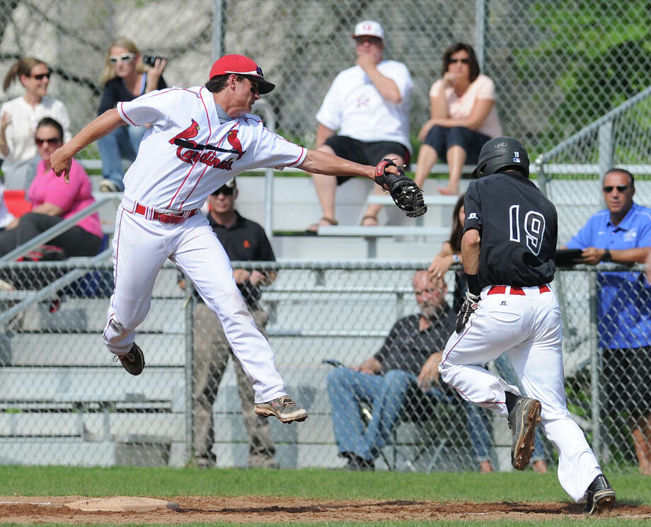 At right, Ryan Pierpont (# 19) of Cheshire is tagged out by Greenwich first baseman Liam O'Neil who made a leaping grab of a high throw in the top of the fourth inning during the Class LL boys high school baseball playoff game between Greenwich High School and Cheshire High School at Greenwich, Wednesday, May 29, 2013. Greenwich defeated Cheshire, 9-2. Photo: Bob Luckey / Greenwich Time