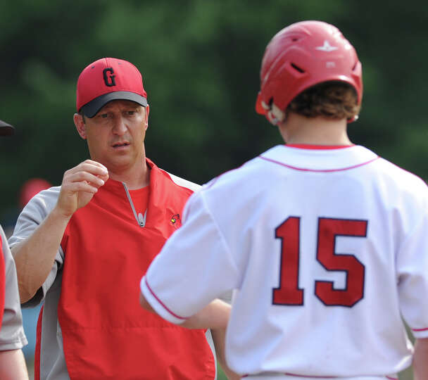 At left, Greenwich baseball coach Mike Mora checks the left forearm of his player, Kyle Dunster, aft