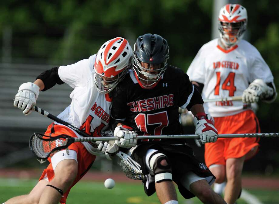 Ridgefield's Martin Carbone, left, fights for the ball with Cheshire's Tyler Sheehan during No. 1 Ridgefield's 19-4 win over No. 17 Cheshire in the first round of the high school boys lacrosse Division L State Tournament at Ridgefield High School in Ridgefield, Conn. on May 29, 2013. Photo: Tyler Sizemore / The News-Times