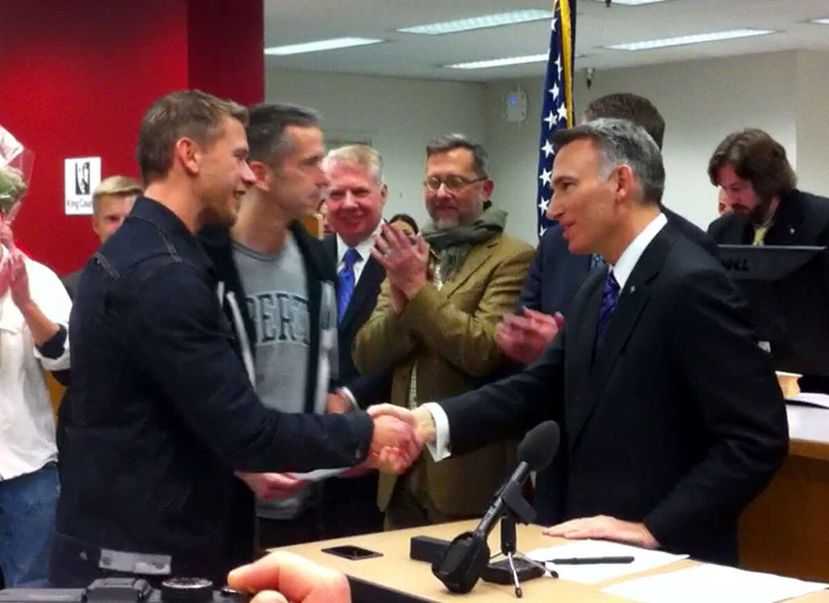 """Dan Savage, Seattle's bigfoot gay journalist -- he writes the """"Savage Love"""" sex-advice column -- shakes hands with King County Executive Dow Constantine and his husband Terry Milleras the couple received their Washington marriage license. The couple previously was married in Canada in 2005."""