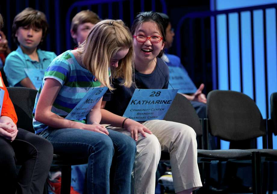 "Katharine Wang, of Beijing, China, right, smiles after getting the word ""quebracho"" correct during the third round of the National Spelling Bee . Mollie Symons, 14, of Kingston, Canada is at left. Photo: Evan Vucci, Associated Press / AP"