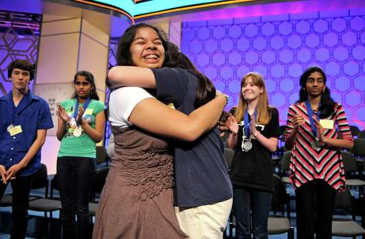 Amber Born, 14, of Marblehead, Mass., center, celebrates with a friend after learning that she will advance to the semifinal round of the Scripps National Spelling Bee. Photo: Cliff Owen, Associated Press / FR170079 AP