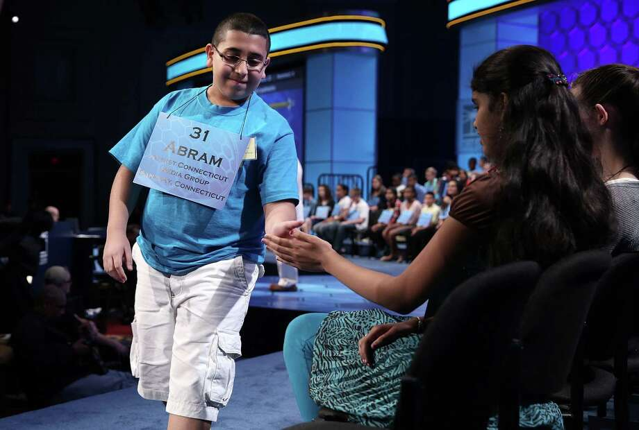 "Abram Mikhaeel Goda (L) of Bridgeport, Connecticut, hi fives with Himanvi Kopuri (R) of Denver, Colorado, after he correctly spelled the word ""nomenclative"" in the round three of the 2013 Scripps National Spelling Bee May 29, 2013 at Gaylord National Resort and Convention Center in National Harbor, Maryland. Spellers competed in the annual spelling contest for the championship. Photo: Alex Wong, Getty Images / 2013 Getty Images"