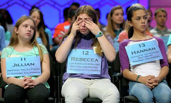 Rebecca Baron of Los Angeles, center, flanked by Jillian Fusi of  El Centro, Calif., left, and Hannah Silvestro of Pomona, Calif., rubs her eyes during the second round of the  Scripps National Spelling Bee. Photo: Cliff Owen, Associated Press / FR170079 AP
